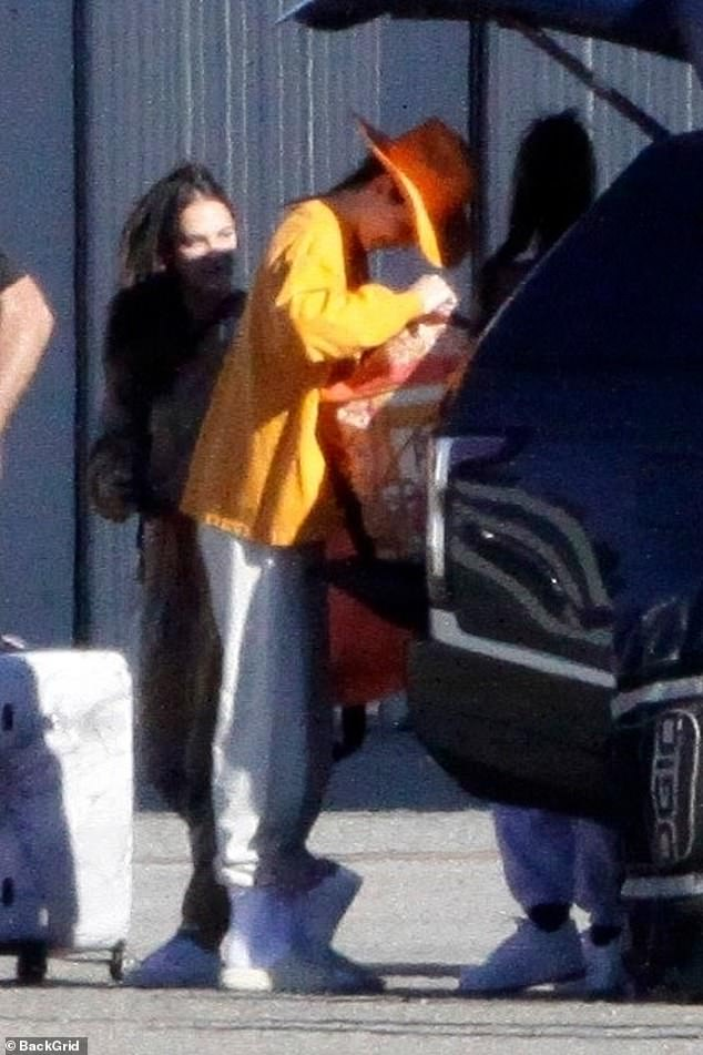 Traveling together: Her older sister Kendall Jenner has met her older sister, and she is wearing a fedora and a yellow shirt.