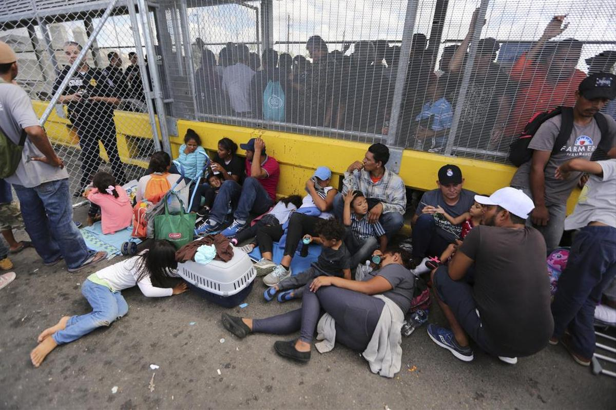 Hope for a better life in the USA: Immigrant families wait at the Gateway International Bridge that connects Matamoros (Mexico) with Brownsville (Texas).