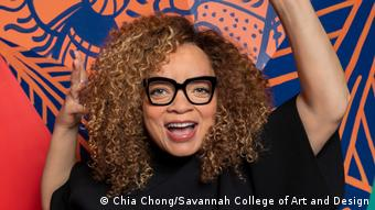 Ruth E. Carter standing on a colorful background.  She laughs widely, her arms lying in the air.