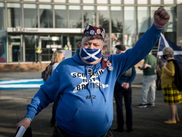 A Scotsman wears a blue and white jacket and a suitable face mask.