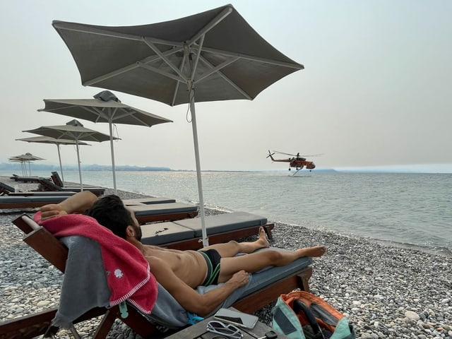 A man sunbathes on a chaise longue on the beach while a helicopter is refueling in the background.