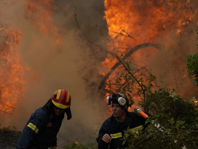 Two firefighters standing near a fire with a hose.