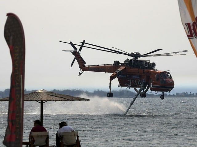 A helicopter resupplying water near the shore.