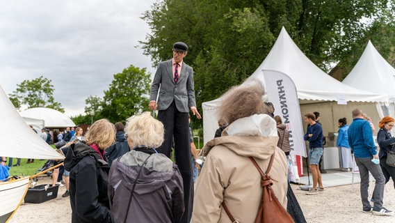 A man on stilts stands before visitors in the square of Guttorf Castle on the occasion of the 75th Citizens' Day of Schleswig-Holstein.  © NDR Photo: Janis Röhlig
